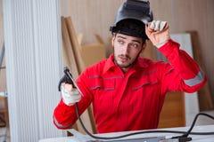 Jeune dépanneur avec une électrode d'arme à feu de soudure et un weldin de casque Photographie stock