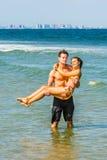 Jeune déplacement américain de couples, détendant sur la plage dans nouveau Je Images stock