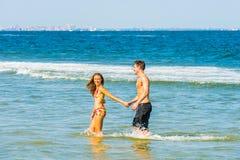 Jeune déplacement américain de couples, détendant sur la plage dans nouveau Je Photos libres de droits