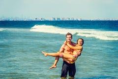 Jeune déplacement américain de couples, détendant sur la plage dans nouveau Je Images libres de droits