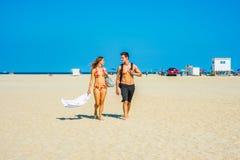 Jeune déplacement américain de couples, détendant sur la plage dans nouveau Je Image stock