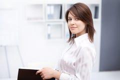Jeune dépliant de fixation de femme d'affaires au bureau photographie stock libre de droits