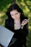 Jeune dame à l'extérieur avec un ordinateur portatif et un téléphone portable Photographie stock