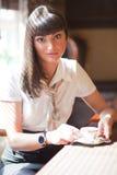 Jeune dame à la fenêtre d'un café Photos stock