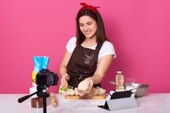 Jeune dame énergique agréable tenant la pâte dans une main, la montrant devant la caméra, ayant le sourire sincère, utilisant tou photos libres de droits