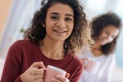 Jeune dame adorable souriant dans l'appareil-photo tout en buvant du thé Photo libre de droits