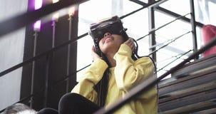 Jeune dame africaine avec son chien enroué sur les escaliers dans l'immeuble de bureaux moderne, femme explorant les verres de VR banque de vidéos