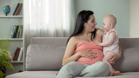 Jeune dame attendant l'enfant, appréciant le temps avec le petit bébé, maternité heureuse photographie stock