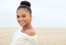 Jeune dame attirante regardant au-dessus de l'épaule et du sourire Photographie stock libre de droits