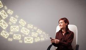 Jeune dame attirante retenant un téléphone avec des graphismes de message Images stock