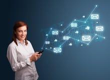 Jeune dame tenant un téléphone avec des flèches et des icônes de message Photos stock