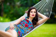 Jeune dame avec de longs cheveux foncés détendant dans l'hamac sur le tropique Photographie stock libre de droits