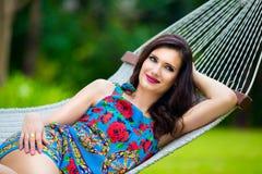 Jeune dame avec de longs cheveux foncés détendant dans l'hamac sur le tropique Images stock