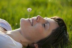 Jeune dame avec la fleur dans sa bouche Photographie stock libre de droits