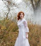 Jeune dame avec les cheveux rouges dans la forêt photo stock