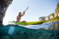 Jeune dame barbotant le kayak photo stock
