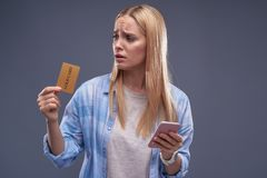 Jeune dame bouleversée avec le téléphone portable regardant la carte d'or images stock