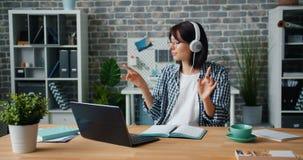 Jeune dame dans des écouteurs fonctionnant avec l'ordinateur portable écoutant la musique dans le bureau banque de vidéos
