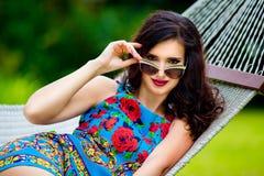Jeune dame dans des lunettes de soleil avec de longs cheveux foncés détendant dans l'hamac Image libre de droits