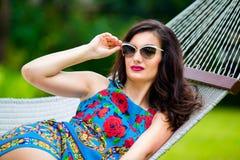 Jeune dame dans des lunettes de soleil avec de longs cheveux foncés détendant dans l'hamac Photos libres de droits