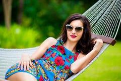 Jeune dame dans des lunettes de soleil avec de longs cheveux foncés détendant dans l'hamac Photographie stock