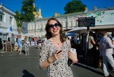 Jeune dame dans des lunettes de soleil buvant du vin Images stock