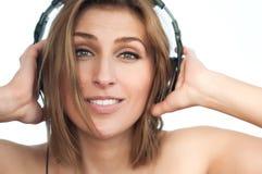 Jeune dame dans la musique de écoute de grands écouteurs Photographie stock libre de droits