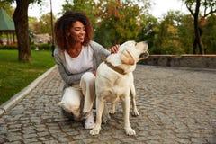 Jeune dame de sourire dans des vêtements sport reposant et étreignant le chien en parc Photos libres de droits