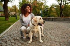 Jeune dame de sourire dans des vêtements sport reposant et étreignant le chien en parc Photographie stock libre de droits