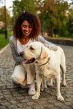 Jeune dame de sourire dans des vêtements sport reposant et étreignant le chien en parc Photos stock