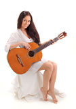 Jeune dame de sourire de brunette jouant la guitare Photographie stock