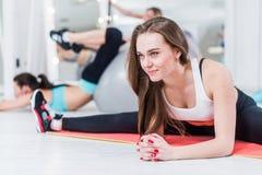 Jeune dame de sourire mignonne dans les vêtements de sport faisant l'exercice fendu de milieu avancé se pliant au-dessus du pench photos libres de droits