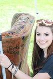 Jeune dame de sourire se tenant sur un divan Image libre de droits
