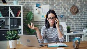 Jeune dame fâchée parlant du téléphone portable dans le bureau discutant des problèmes au travail clips vidéos