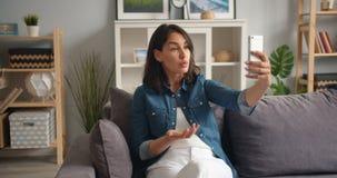 Jeune dame fâchée parlant sur le smartphone faisant l'appel visuel faisant des gestes à la maison banque de vidéos