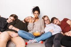 Jeune dame fâchée regardant tristement in camera et mangeant des chips tandis que ses amis presque dormant à la maison photographie stock libre de droits