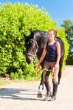 Jeune dame gaie équestre menant son cheval foncé images stock