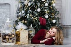 Jeune dame heureuse avec de longs cadeaux de cheveux par la cheminée près de l'arbre de Noël image stock