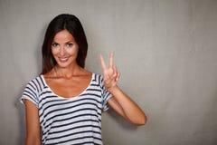 Jeune dame heureuse célébrant avec le signe de victoire images libres de droits