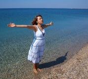 Jeune dame heureuse restant sur un littoral images libres de droits