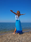 Jeune dame heureuse restant sur un littoral photos libres de droits