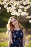Jeune dame heureuse se tenant dans l'arbre de floraison Photos libres de droits
