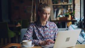 Jeune dame heureuse travaillant avec l'ordinateur portable dans se reposer de dactylographie de café seule à la table banque de vidéos