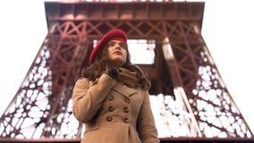 Jeune dame intéressée tenant Tour Eiffel proche seul, ami de attente Photos stock