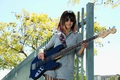 Jeune dame jouant la guitare basse bleue dehors Photographie stock