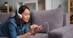 Jeune dame joyeuse touchant l'écran de smartphone écoutant la musique dans des écouteurs banque de vidéos