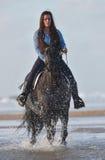 Jeune dame montant un cheval à la plage dans le début de la matinée photographie stock libre de droits