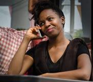 Jeune dame noire au téléphone se reposant à la table à l'outd Image stock