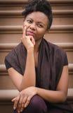Jeune dame noire s'asseyant sur la pensée d'étape Photos stock