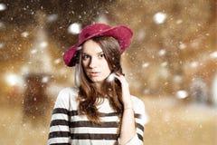 Jeune dame réfléchie dans le chapeau souple rouge l'hiver Photographie stock libre de droits